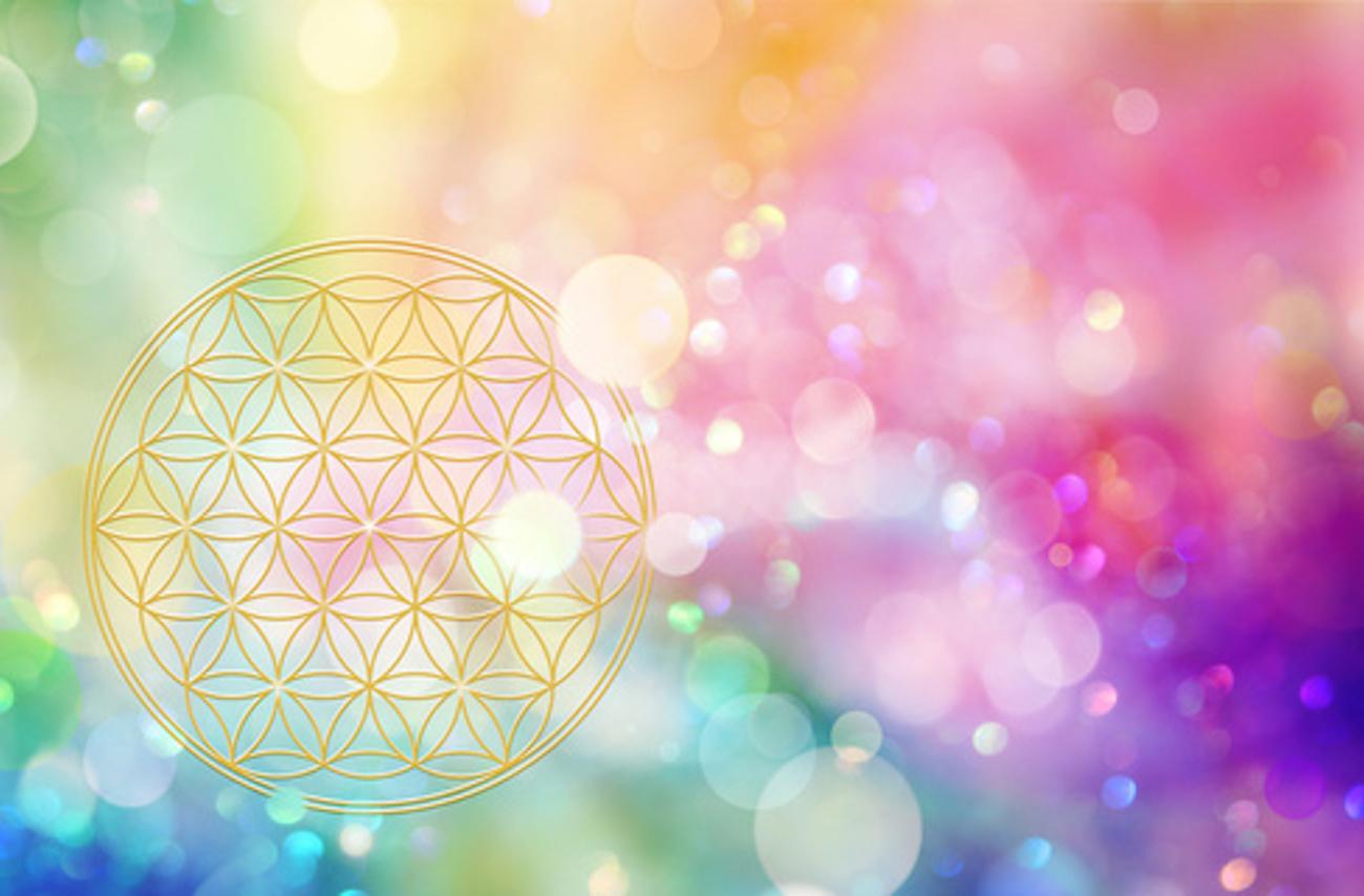 Aus der Blume des Lebens erstrahlt regenbogenfarbenes Licht