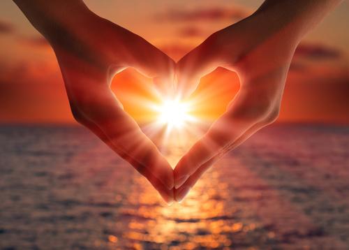 coucher de soleil dans le coeur formé par les mains