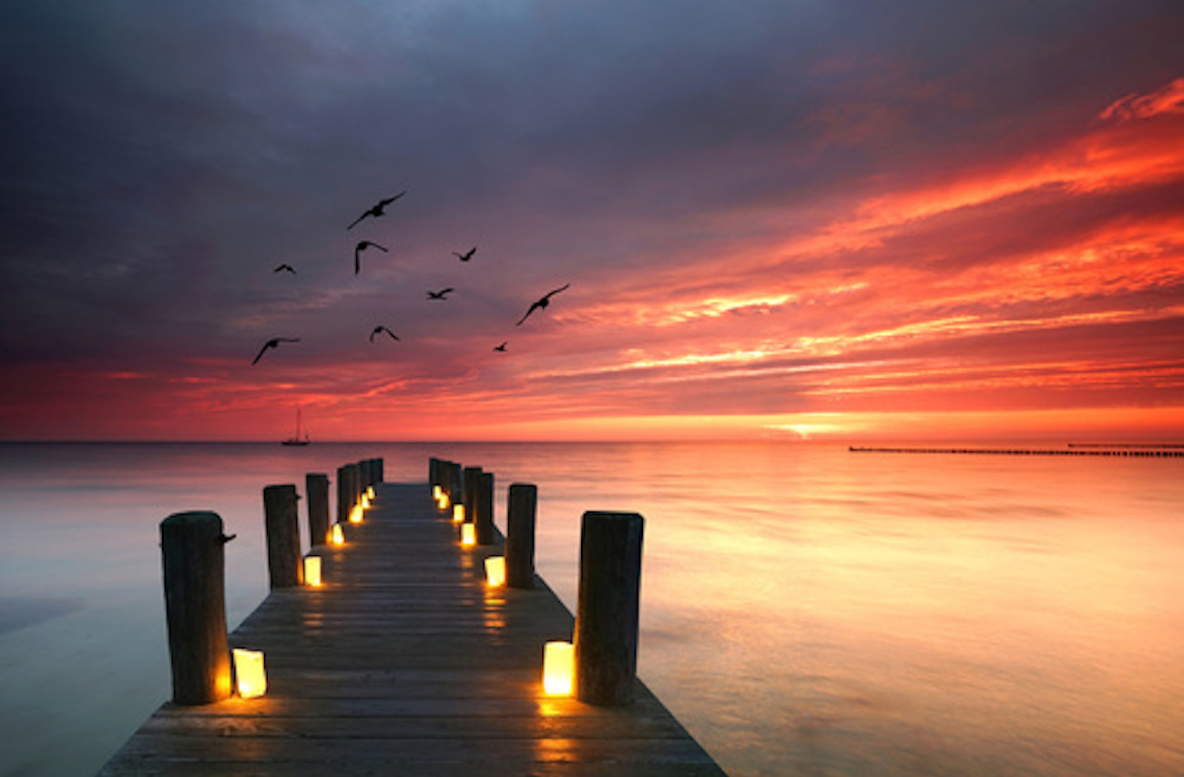 ponton illuminé par des bougies coucher de soleil oiseaux